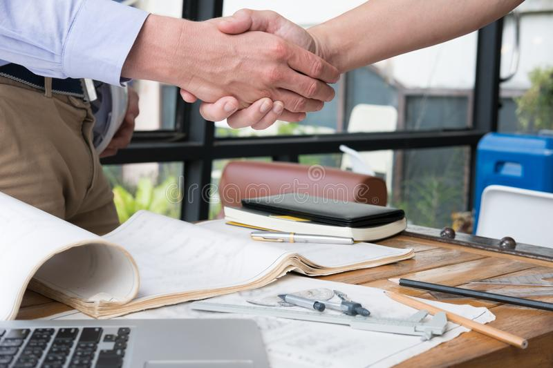 Engineer handshaking for successful deal in construction plan. a royalty free stock photos