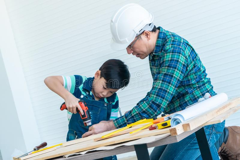 Engineer Handy Father is teaching his boy to use electric driller on wood royalty free stock images