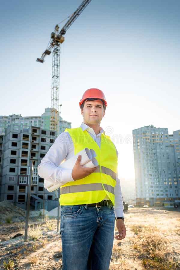 Engineer in hardhat and yellow jacket posing with blueprints stock photo