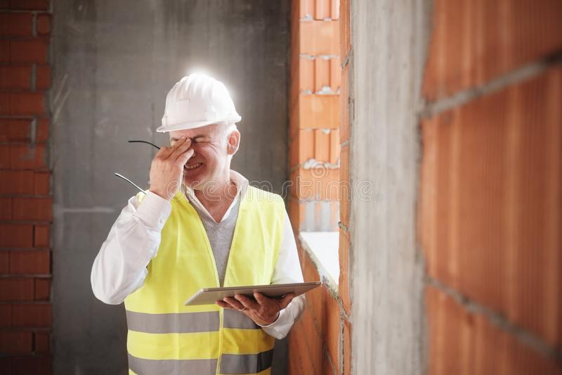 Engineer With Headache At Work With Computer In Construction Site stock photo