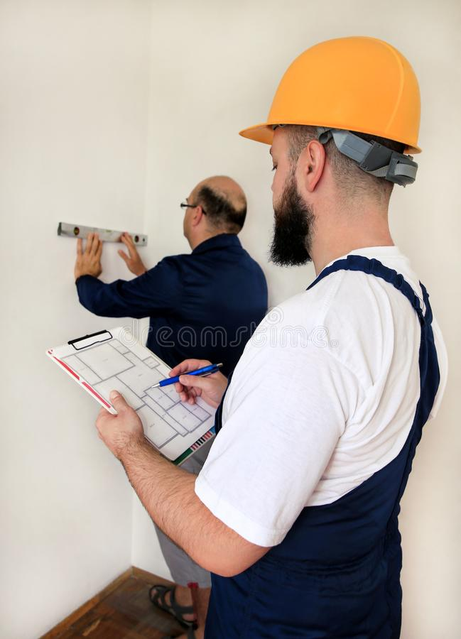 Engineer with his colleague, construction worker is measuring wall using spirit level tool, checking in apartment blueprint. Engineer, contractor and project stock image