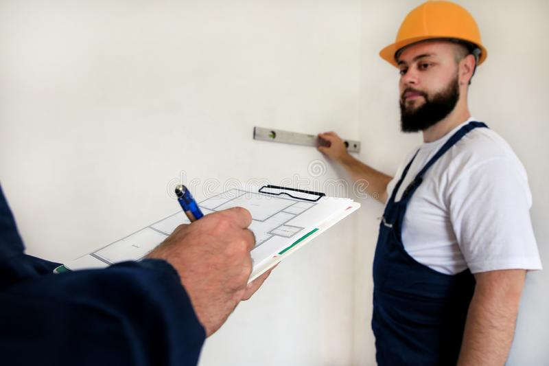 Engineer with his colleague, construction worker is measuring wall using spirit level tool, checking in apartment blueprint. Engineer, contractor and project royalty free stock photography