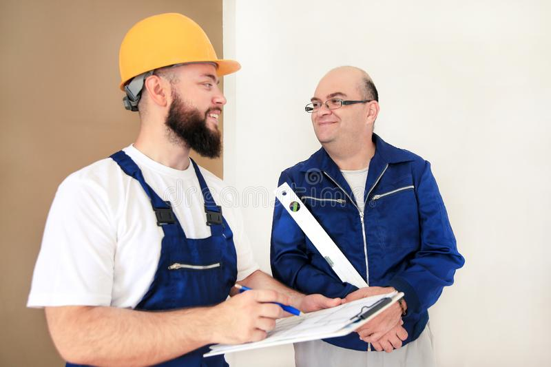 Engineer with his colleague, construction worker is measuring wall using spirit level tool, checking in apartment blueprint. Engineer, contractor and project stock photography