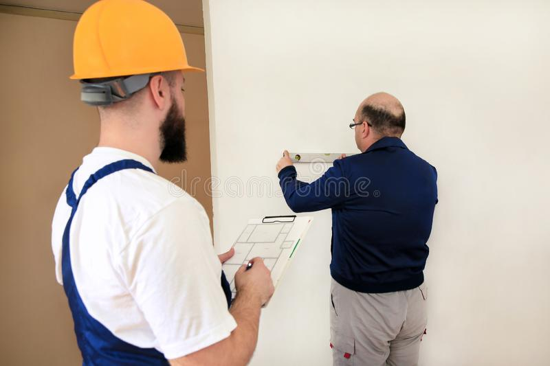 Engineer with his colleague, construction worker is measuring wall using spirit level tool, checking in apartment blueprint. Engineer, contractor and project stock photos