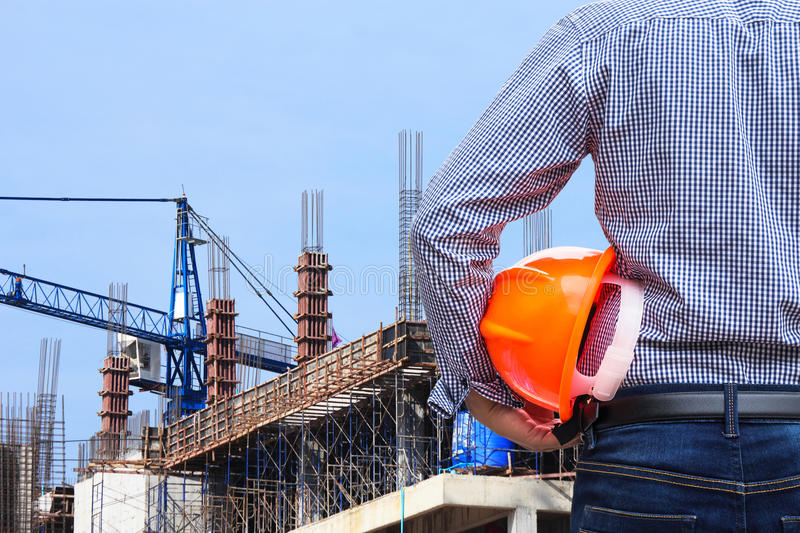 Engineer holding yellow safety helmet in building construction site with crane. On blue sky background stock image