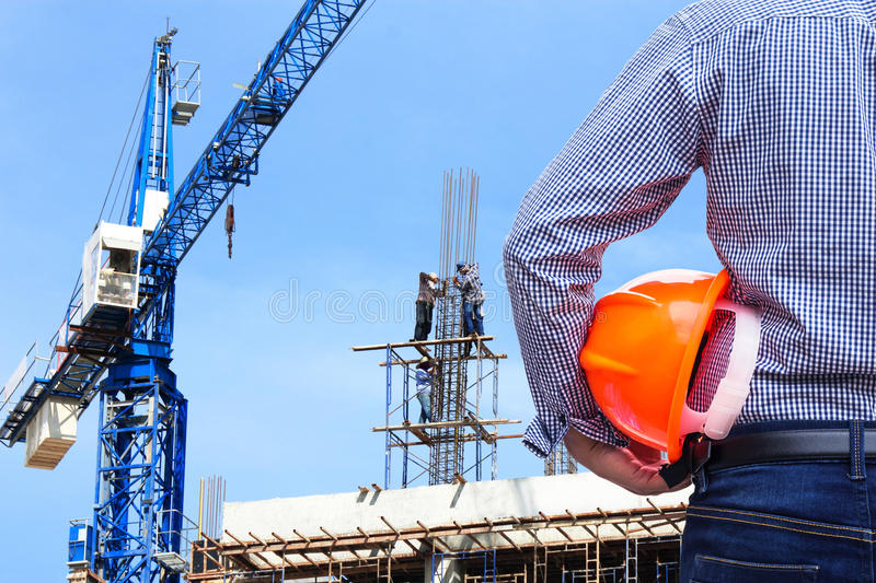 Engineer holding yellow safety helmet in building construction site with crane. On blue sky background stock photo