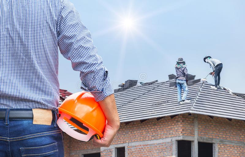 Engineer holding yellow safety helmet at new home building with workers installing concrete tile. Resident engineer holding yellow safety helmet at new home royalty free stock image
