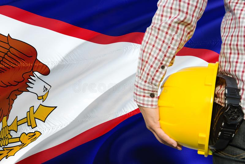 Engineer is holding yellow safety helmet with waving American Samoa flag background. Construction and building concept royalty free stock photography