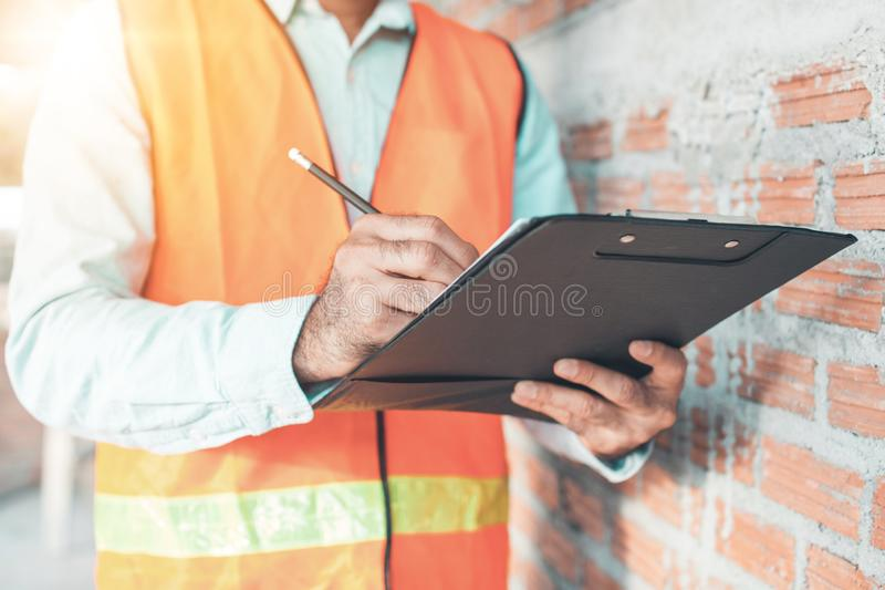Engineer or inspector checking progressing work in construction site royalty free stock image