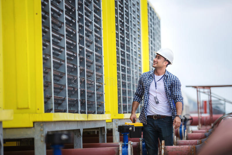 Engineer inspects the large air conditioner with a happy smile. royalty free stock images