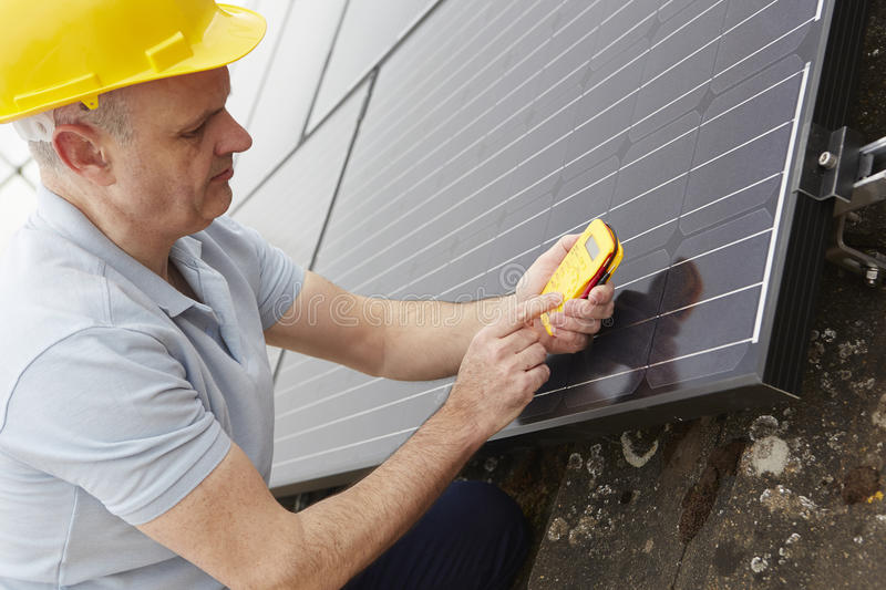 Engineer Installing Solar Panels On Roof Of House. Engineer Installs Solar Panels On Roof Of House royalty free stock image
