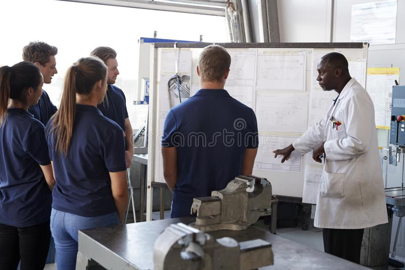 Engineer instructing apprentices at a whiteboard, close up stock photo