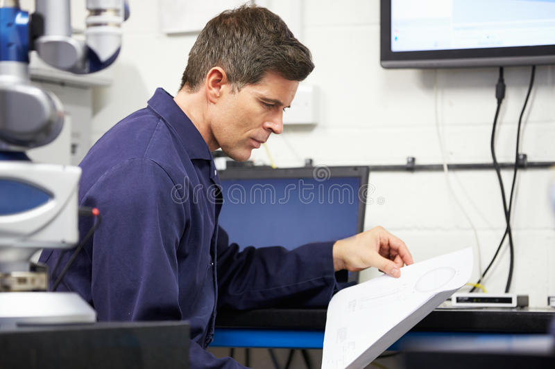 Engineer Looking At Plans With CMM Arm In Foreground royalty free stock images