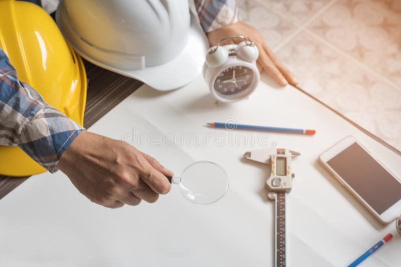 Engineer with magnify glass for looking blank paper for new project. Engineer and Architecture concept, Business theme. Engineer with magnify glass for looking stock images