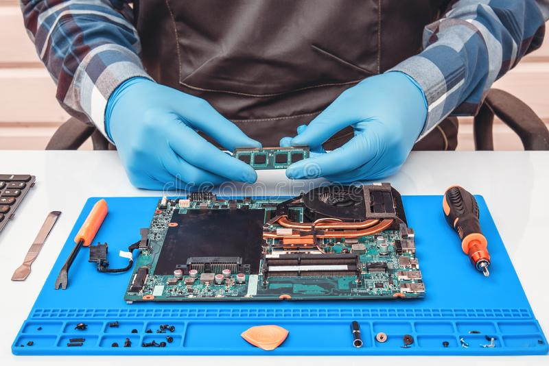 Engineer makes dismantling of RAM for disassembling and repairing a laptop. Engineer makes dismantling of RAM for disassembling and repairing a laptop stock photo