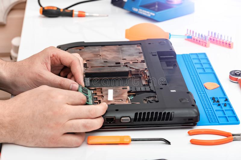 Engineer makes dismantling of RAM for disassembling and repairing a laptop. Engineer makes dismantling of RAM for disassembling and repairing a laptop royalty free stock images