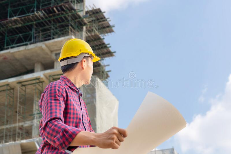 Engineer man with clipping path checking and planning project at construction site, Man holding blueprint and looking into the sky royalty free stock photo