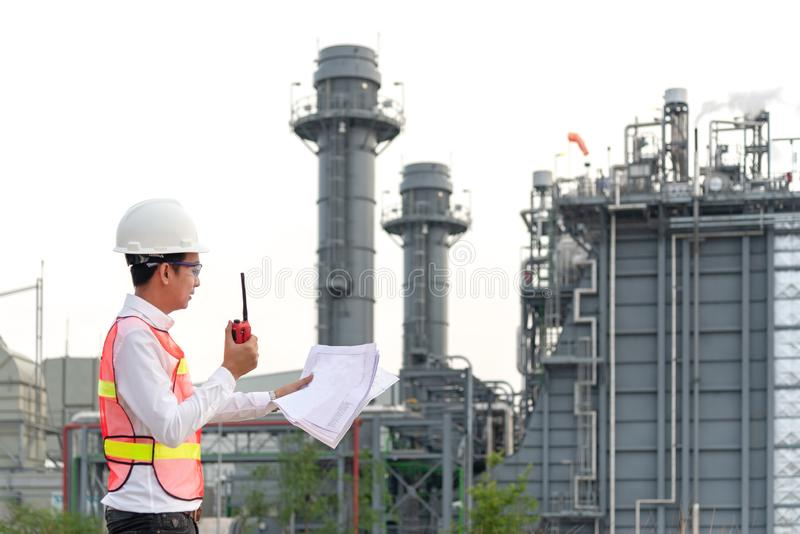 Engineer man holding blueprint with radio for workers security control at power plant energy and petrochemical industry. stock image