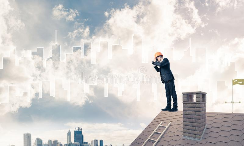 Engineer man standing on roof and looking in binoculars. Mixed m royalty free stock image
