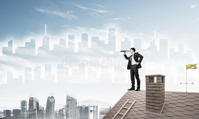 Engineer man standing on roof and looking in spyglass. Mixed med. Young businessman in suit on roof edge. Mixed media stock images