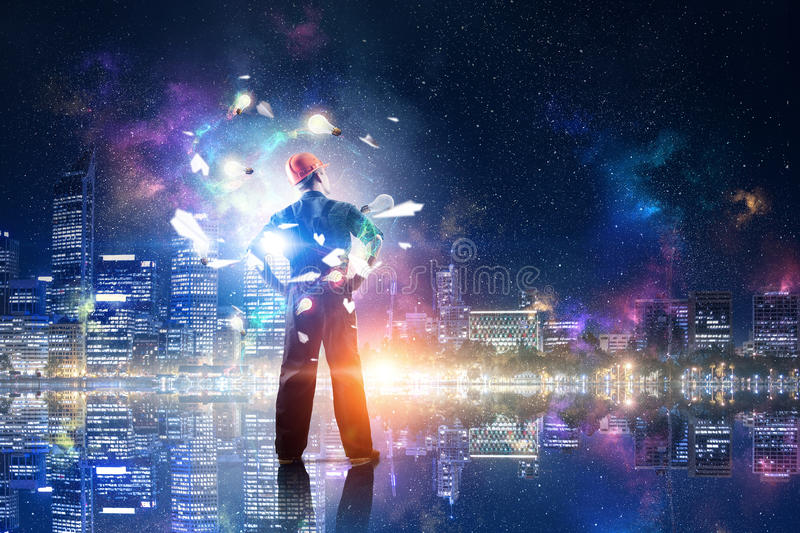 Engineer man viewing cityscape . Mixed media royalty free stock photography