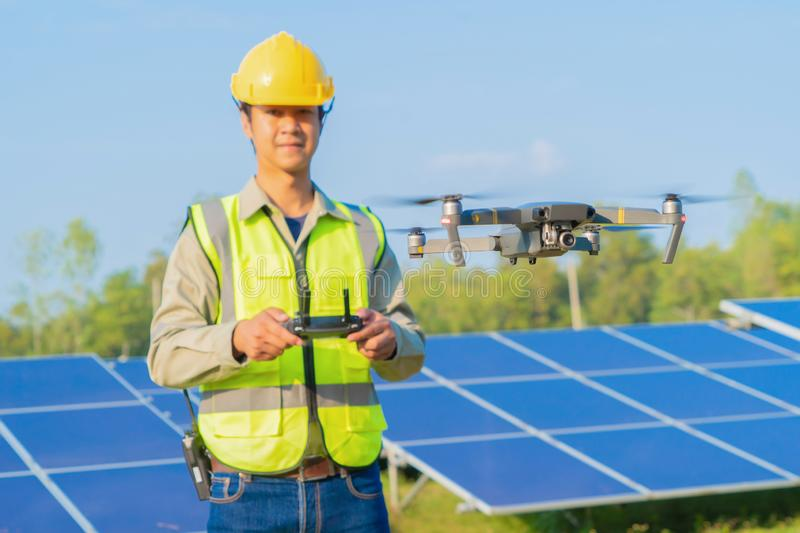 Engineer man or worker, people, using a drone to survey. Solar panels or solar cell on the roof in farm. Power plant with green stock images