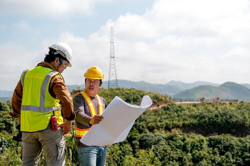Engineer manager man discuss with his team who hold construction plan and stay in front of mountain view and  high voltage pole stock photography