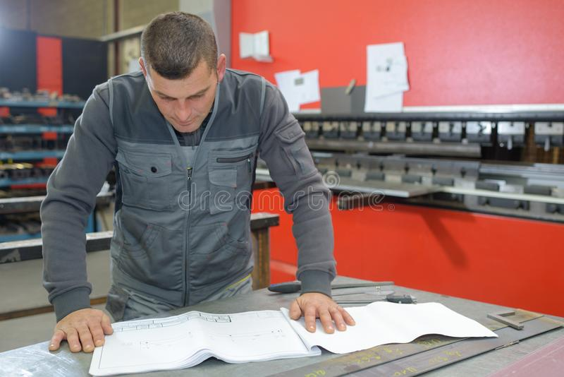 Engineer in mechanical factory reading instructions royalty free stock photography