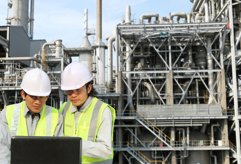 Engineer oil refinery. Discussion with laptop on location site stock image