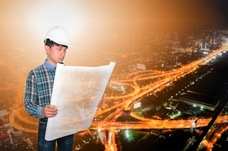 Engineer open hold blueprints in construction concept with night city Blurred background.  royalty free stock image