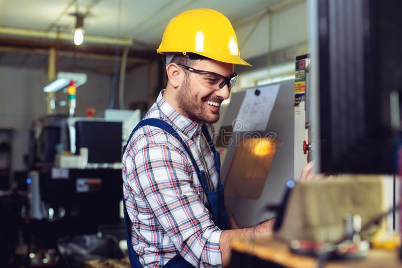 Engineer Operating CNC Machinery In Factory royalty free stock photo