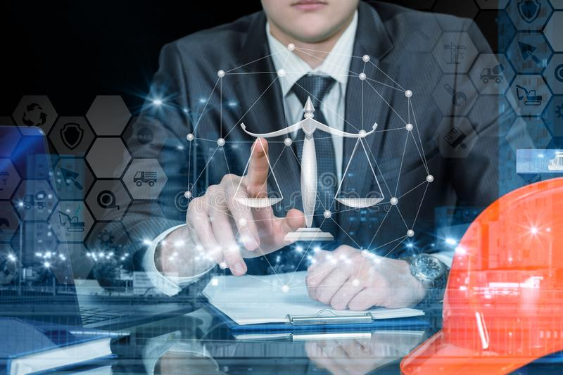 An engineer operating with juridical scales and financial system. A closeup of a businessman sitting at the table and operating with the comb financial system of stock images