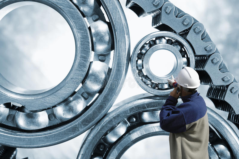 Engineer pointing at ball-bearings and chains royalty free stock photos