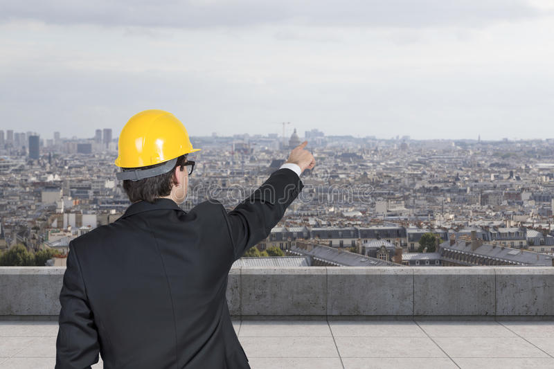 Engineer pointing at skyscraper royalty free stock photo