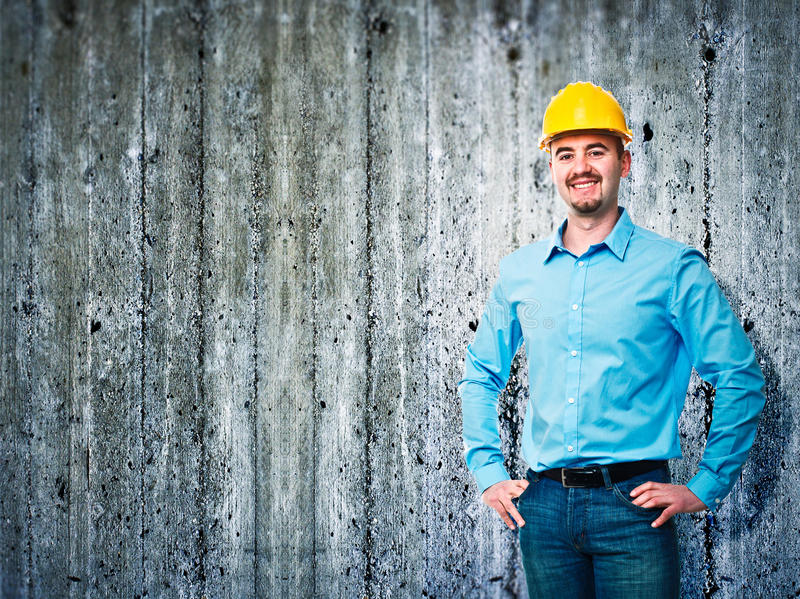 Engineer portrait. Smiling worker and concrete texture background stock photography