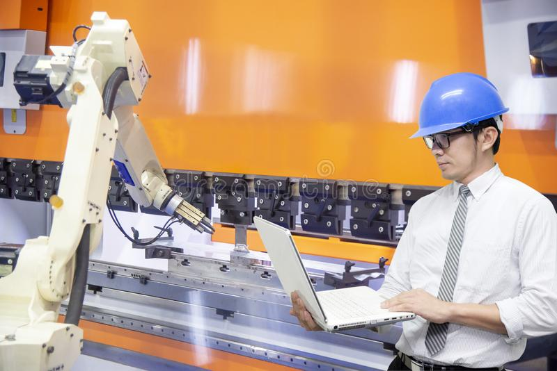 The engineer programming the robotic arms for loading the sheet metal to the hydraulic bending machine. royalty free stock images