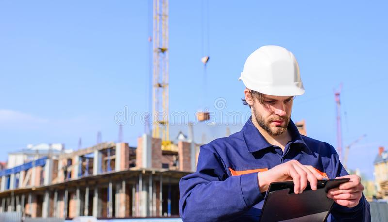 Engineer protective helmet stand in front of blue sky background. Contractor control according to plan. Builder engineer stock images