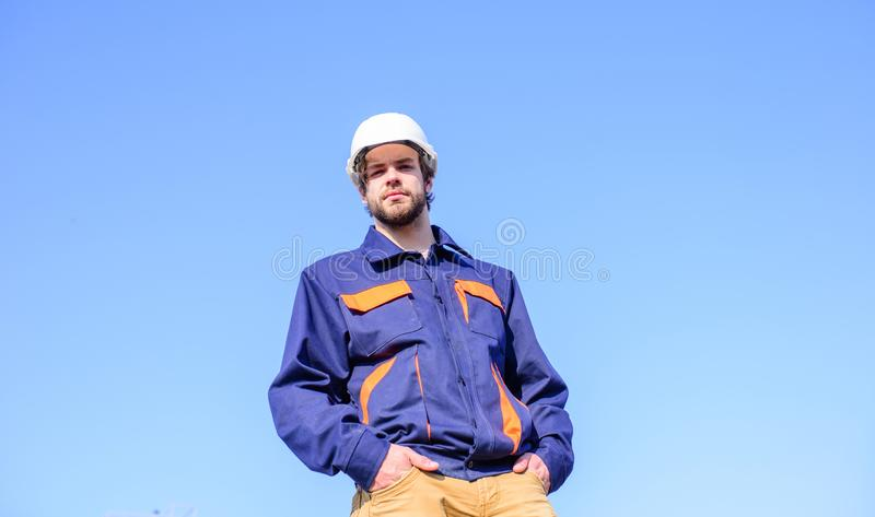 Engineer protective helmet stand in front of blue sky background. Foreman control construction process. Contractor stock photography