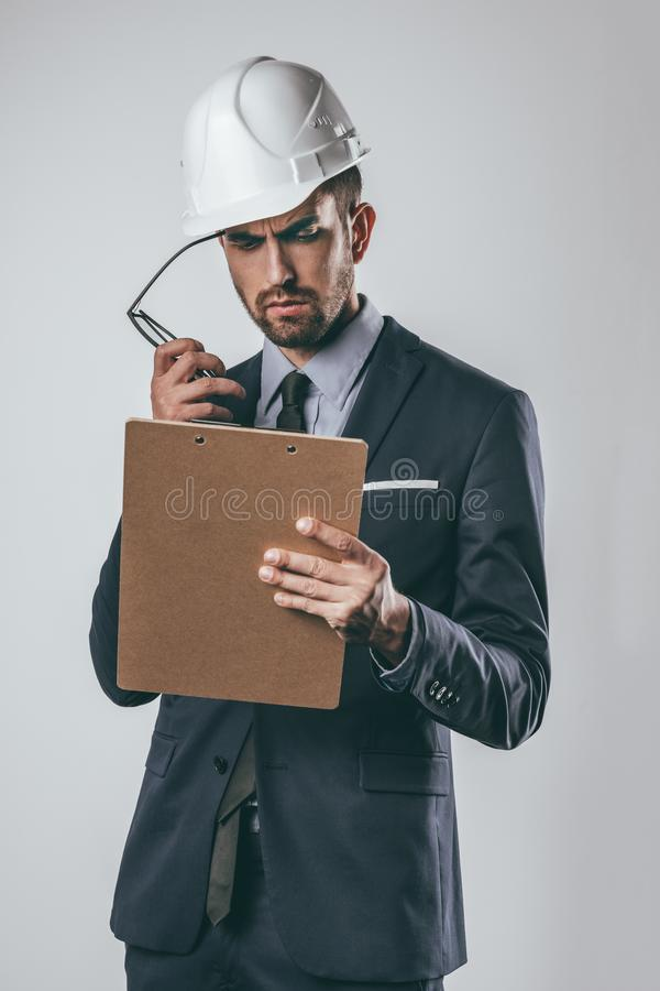 Engineer reading clipboard and scratching temple royalty free stock image