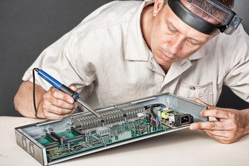 Engineer repairing circuit board. In computer equipment royalty free stock photo