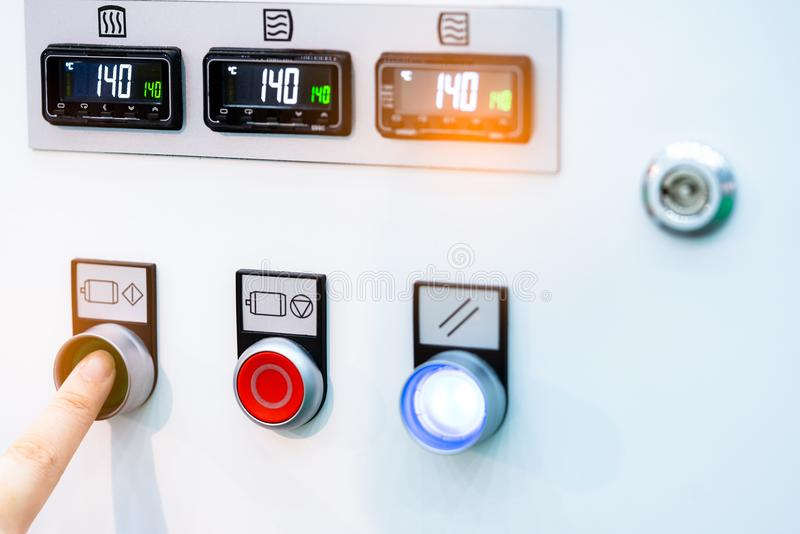 Engineer`s hand push green button to open temperature control machine. Temperature control panel cabinet contain digital screen. Display for temperature gauge stock images