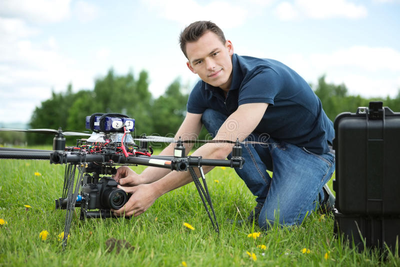 Engineer Setting Camera On Photography Drone. Portrait of confident young engineer setting camera on photography drone in park stock photography