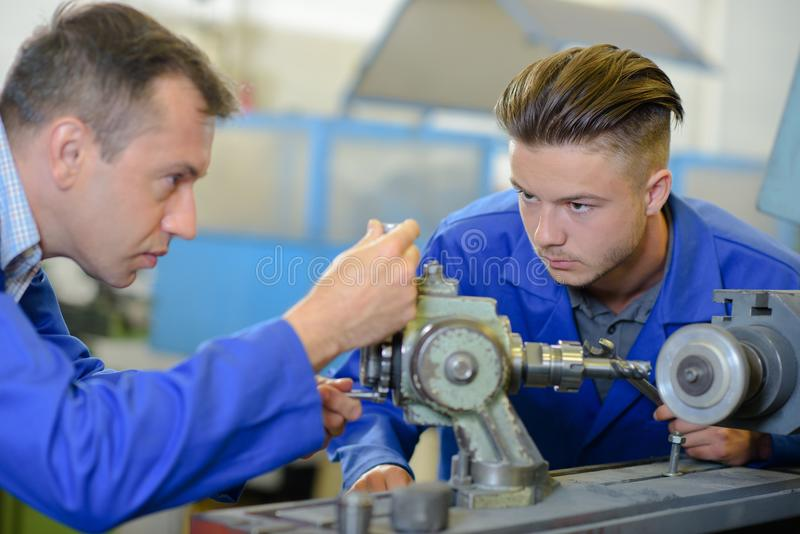 Engineer setting up equipment being watched by apprentice stock photography