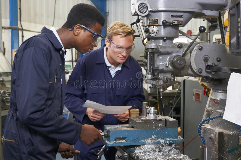 Engineer Showing Apprentice How to Use Drill In Factory. Experienced Engineer Showing Apprentice How to Use Drill In Factory stock image