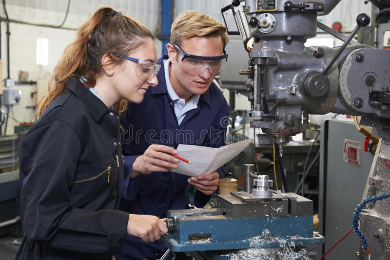 Engineer Showing Apprentice How to Use Drill In Factory. Engineer Showing Female Apprentice How to Use Drill In Factory royalty free stock images
