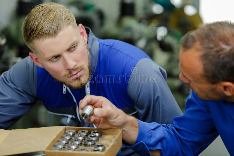 Engineer showing metal components to apprentice. Engineer stock photography
