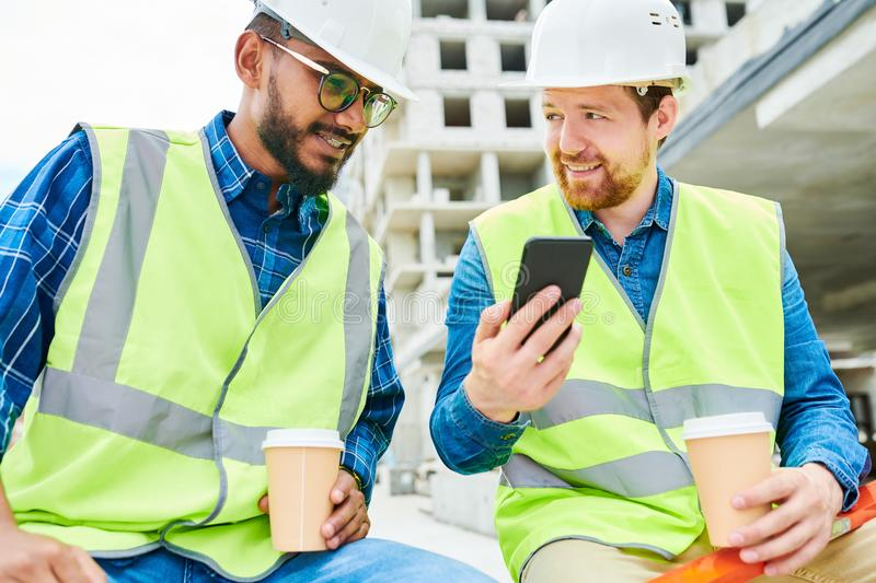 Engineer showing smartphone to colleague during break stock photo