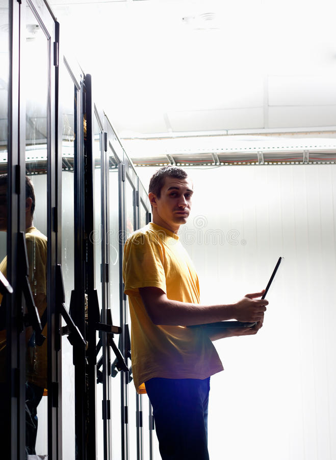 The engineer sits front equipment. In datacenter and configuring equipment stock photography