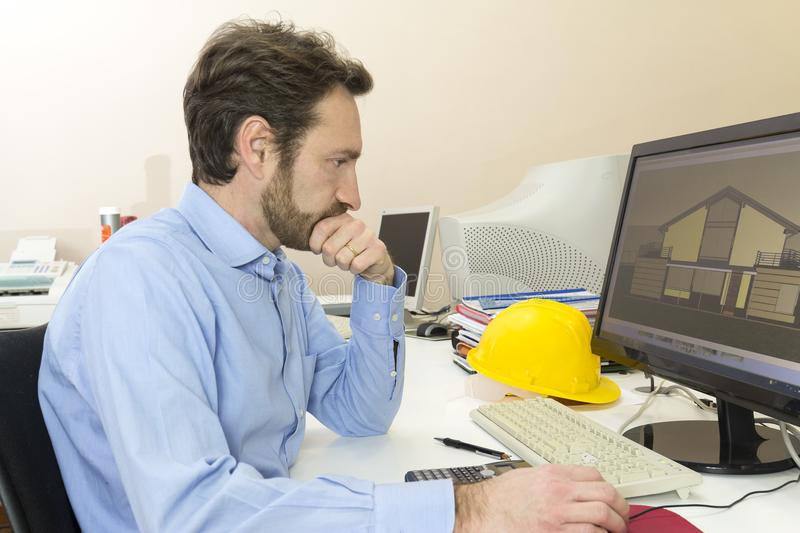 Engineer sitting in front of the computer in his office. Engineering: Engineer sitting in front of the computer in his office stock photography