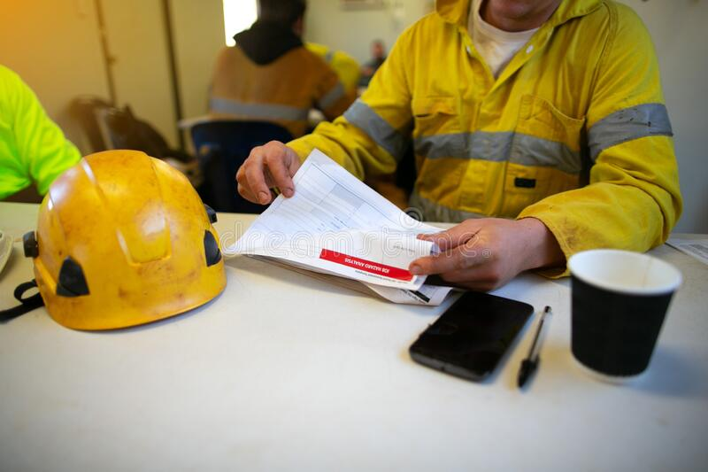 Engineer sitting placing safety hard hat on the table coffee cup pen reviewing JSA risk assessment stock photo
